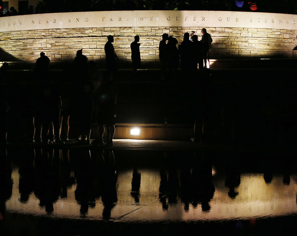 Photo - People are silhouetted underneath the Survivor Tree at the Oklahoma City National Memorial before the Oklahoma City Memorial Marathon in Oklahoma City, Sunday, April 24, 2016. Photo by Nate Billings, The Oklahoman