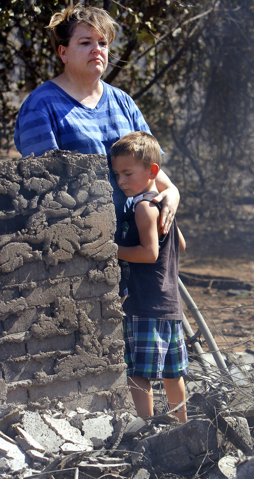 Photo - Tracy Streeper comforts five year-old grandson Jesse, as they stand on the north side of Streeper's destroyed home. The Streepers had lived in this house for one year. Residents  in Luther were allowed to return to the their homes early Saturday, Aug. 4, 2012, after they fled a rapidly moving wildfire yesterday that consumed at least seven structures on South Dogwood Street, leaving smoldering ashes where family homes once stood.  