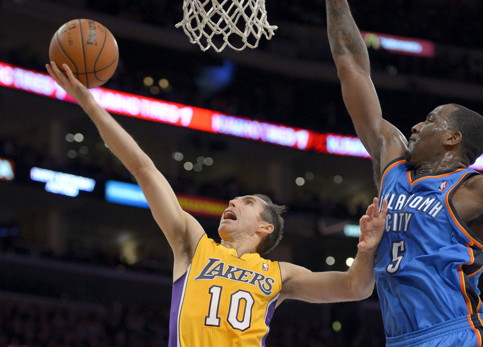 Photo - Los Angeles Lakers guard Steve Nash, left, shoots around Oklahoma City Thunder center Kendrick Perkins during the first half of their NBA basketball game, Friday, Jan. 11, 2013, in Los Angeles. (AP Photo/Mark J. Terrill)