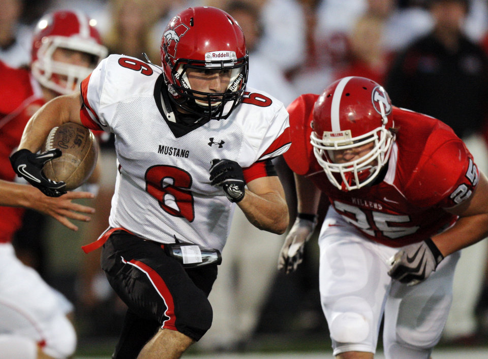 Photo - Mustang's David Glidden gets past Yukon's Kurien Cary on his way to returning a kick for a touchdown during the high school football game between Mustang and Yukon at Yukon High School in Yukon, Okla., Friday, Sept. 3, 2010. Photo by Nate Billings, The Oklahoman