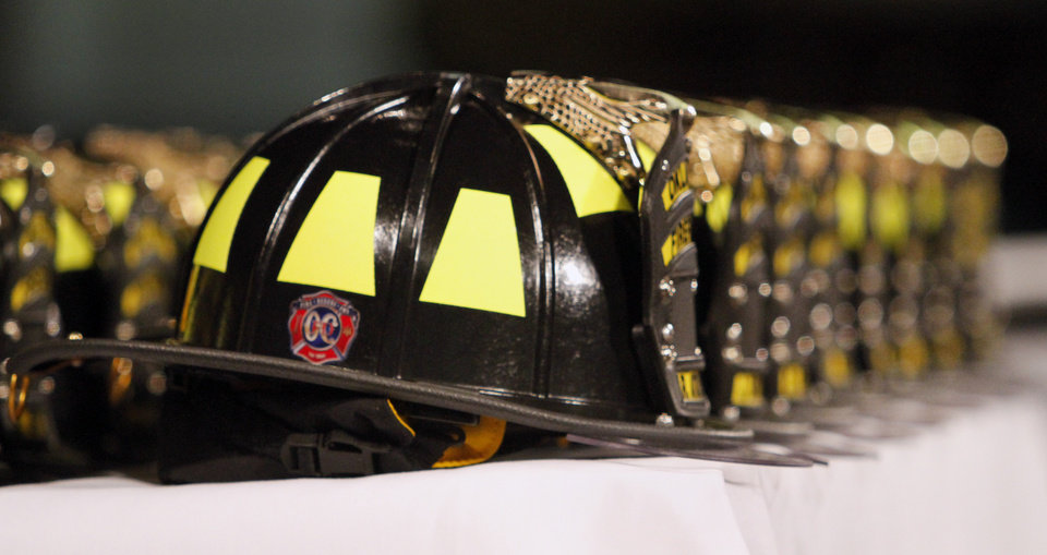 Firefighters helmets line a table during Oklahoma City Fire Department's recruit  class of 2011-12  graduation at Crossroads Church in Oklahoma City, Friday, February 10, 2012. The class had 29 recruits graduating from the training class. Photo By Steve Gooch, The Oklahoman