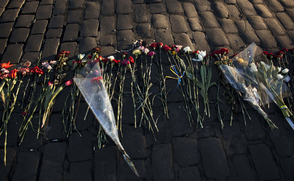 Photo - Flowers placed by people in memory of those who died in late February's clashes are lit by the early morning sun in Kiev's Independence Square, Ukraine, Tuesday, March 11, 2014. (AP Photo/David Azia)