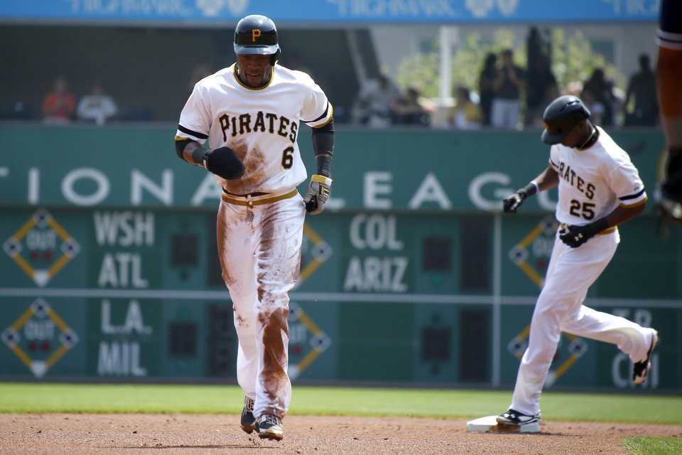 Photo - Pittsburgh Pirates' Starling Marte (6) is chased from second as teammate Gregory Polanco rounds the base after hitting a two-run home run in the first  inning of the baseball game against the San Diego Padres on Sunday, Aug. 10, 2014, in Pittsburgh. (AP Photo/Keith Srakocic)