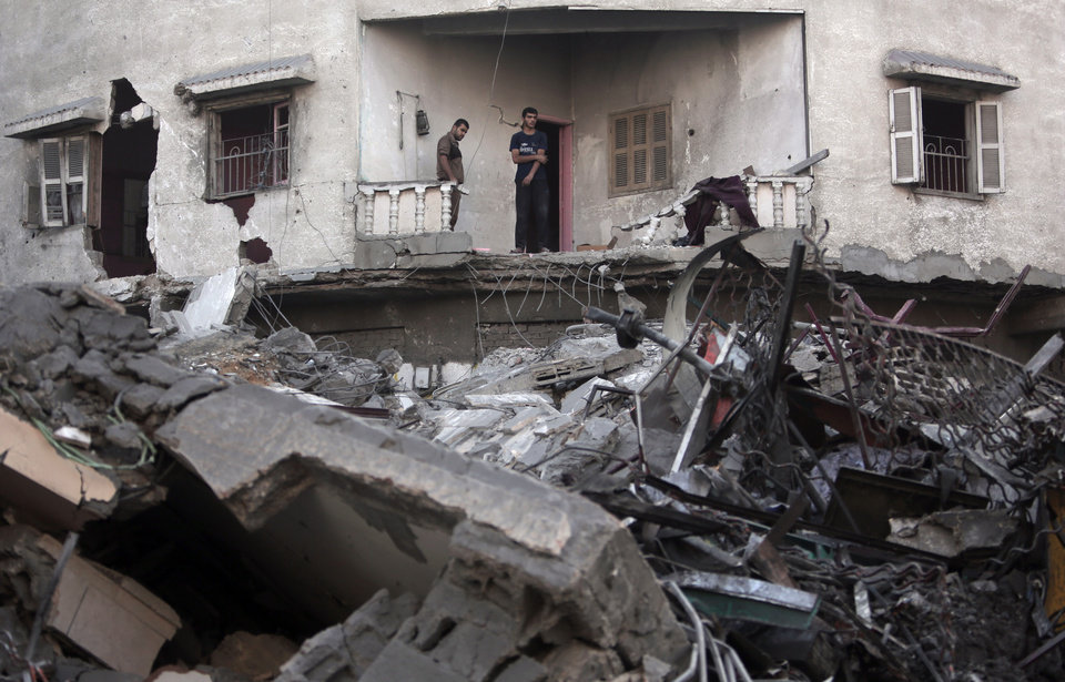 Photo - Palestinians look at the rubble of the 15-story Basha Tower that was destroyed in early morning Israeli airstrikes in Gaza City, Tuesday, Aug. 26, 2014.  Israel bombed two Gaza City high-rises with dozens of homes and shops Tuesday, collapsing the 15-story Basha Tower and severely damaging the Italian Complex in a further escalation in seven weeks of cross-border fighting with Hamas. Both buildings were evacuated after receiving warnings of impending strikes. (AP Photo/Khalil Hamra)