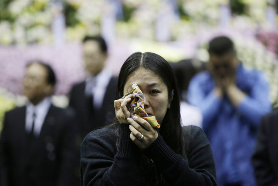 Photo - Lee Won-a, 40, wipes her tears after paying tribute to the victims of the sunken ferry Sewol, at a memorial altar in Ansan, south of Seoul, South Korea, Wednesday, April 30, 2014. Two weeks after the ferry sank off South Korea's southern cost, divers have recovered scores of bodies from the wreckage, but they fought strong currents and floating debris inside the ship Wednesday as they searched for the rest still missing. (AP Photo/Lee Jin-man)