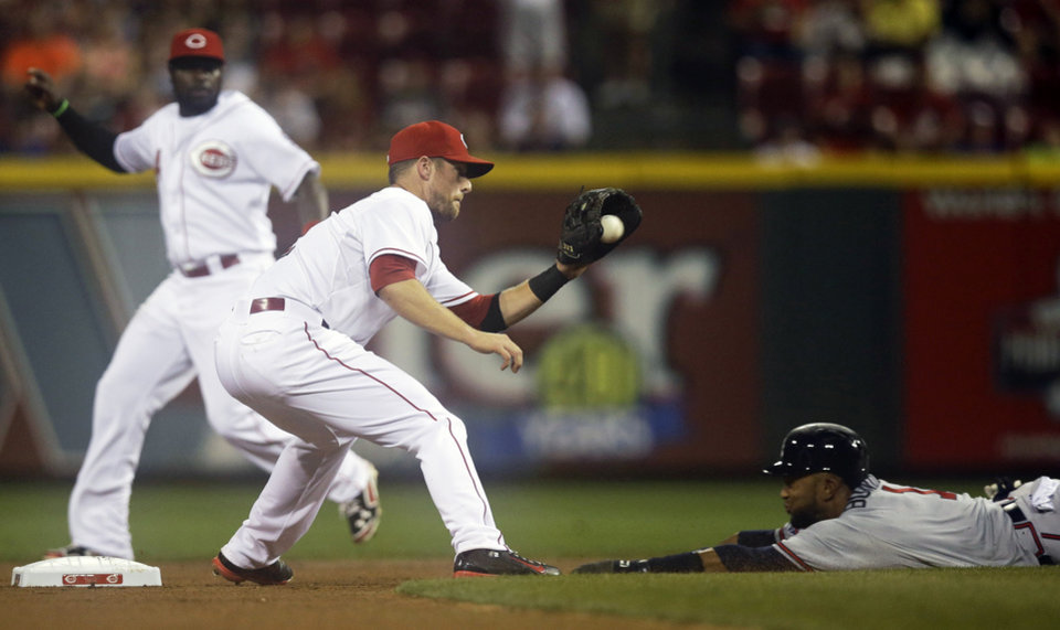 Photo - Atlanta Braves' Emilio Bonifacio, right, is out trying to steal second base as Cincinnati Reds shortstop Zack Cozart catches the throw from catcher Brayan Pena in the first inning of a baseball game, Saturday, Aug. 23, 2014, in Cincinnati. Second baseman Brandon Phillips waches at left. (AP Photo/Al Behrman)