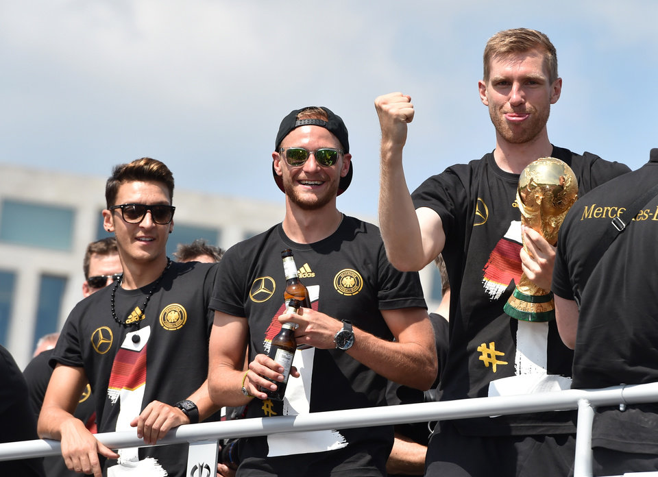 """Photo - German national soccer players, from left,  Mesut Özil, Benedikt Hoewedes  and Per Mertesacker , celebrate as they tour Berlin by bus  Tuesday July 15, 2014.  Germany's World Cup-winning team has returned home  from Brazil to celebrate the country's fourth title with huge crowds of fans. The team's Boeing 747 touched down at Berlin's Tegel airport midmorning Tuesday after flying a lap of honor over the """"fan mile"""" in front of the landmark Brandenburg Gate. (AP Photo/dpa, Jens Kalaene)"""