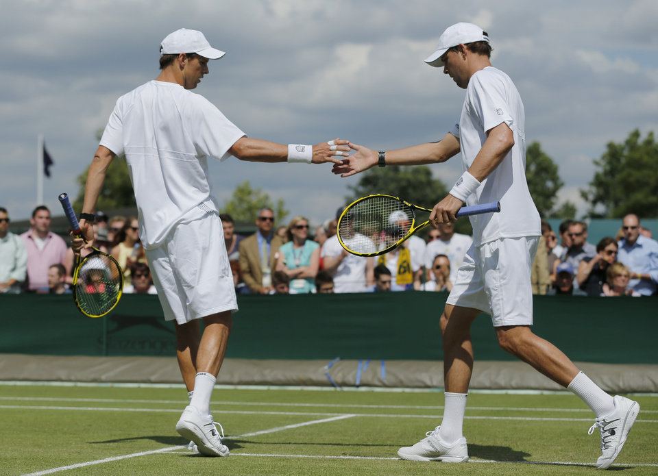 Photo - Mike Bryan, left, and Bob Bryan both of the U.S. touch hands as they play a men's doubles match against Matthew Ebden of Australia and Samuel Groth of Australia plays at the All England Lawn Tennis Championships in Wimbledon, London, Friday, June 27, 2014. (AP Photo/Ben Curtis)
