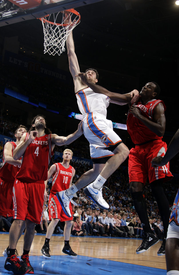 Photo - Oklahoma City's Nick Collison (4) shoots in between Houston's Luis Scola (4) and Samuel Dalembert (21) during the NBA basketball game between the Oklahoma City Thunder and the Houston Rockets at the Chesapeake Energy Arena, Tuesday, March 13, 2012. Photo by Sarah Phipps, The Oklahoman.