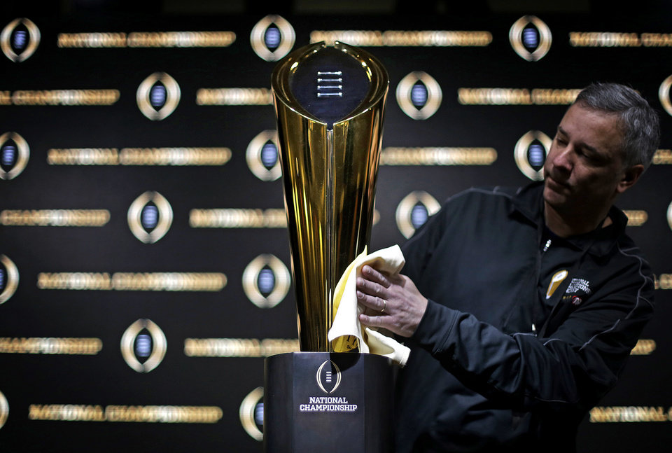 Photo - Charley Green buffs the NCAA college football championship trophy before a coaches press conference in Atlanta, Sunday, Jan. 7, 2018. Georgia and Alabama will be playing for the NCAA football national championship on Monday, Jan. 8. (AP Photo/David Goldman)