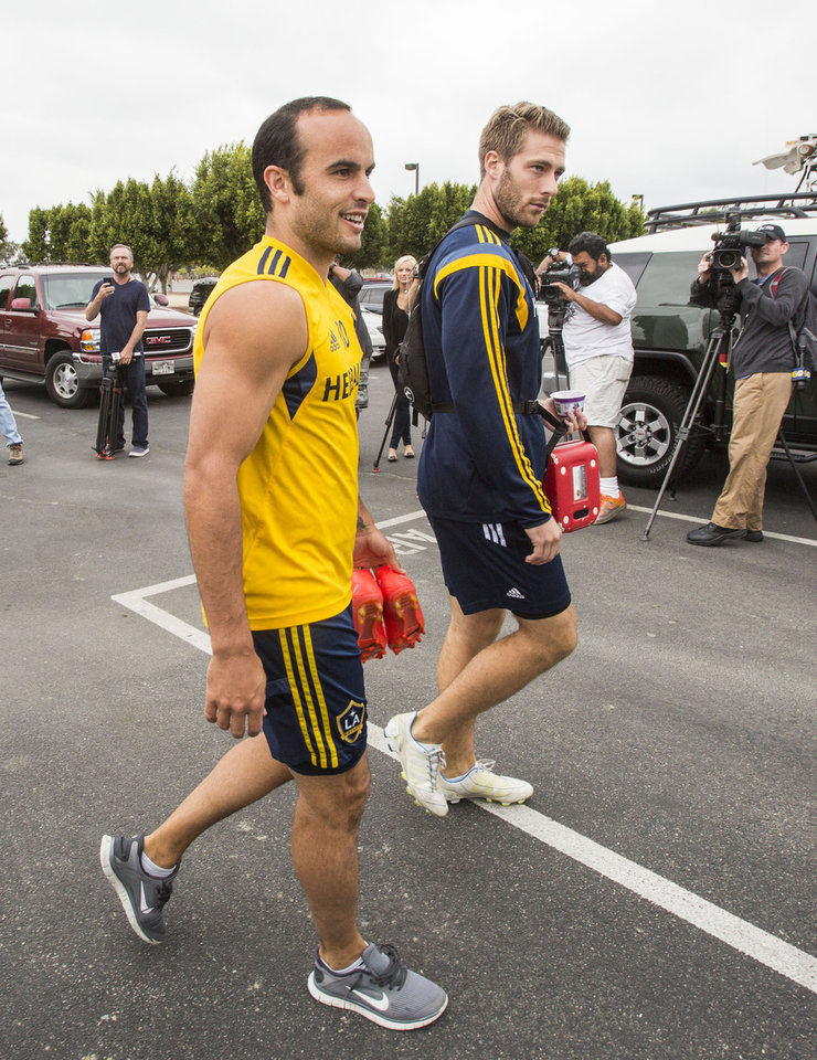 Photo - Los Angelese Galaxy forward Landon Donovan, left, arrives for a training session at StubHub Center in Carson, Calif., Saturday, May 24, 2014. Donovan, the most accomplished American player in the history of men's soccer, won't be going to his fourth World Cup. The 32-year-old attacker was among seven players cut Thursday when coach Jurgen Klinsmann got down to the 23-man limit well before the June 2 deadline. (AP Photo/Ringo H.W. Chiu)