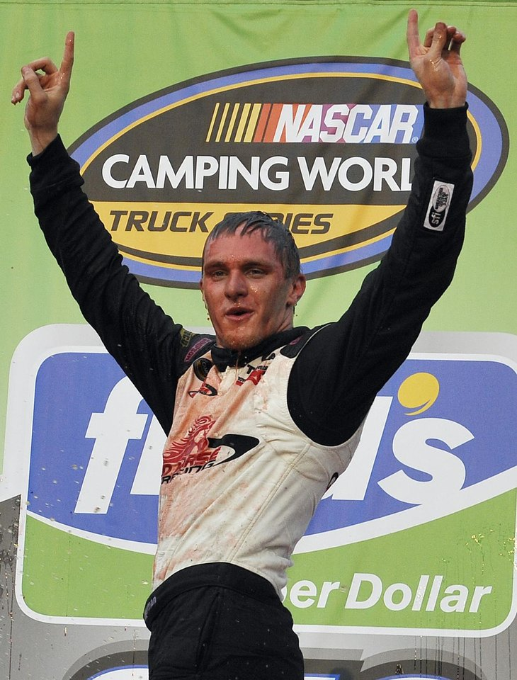 NASCAR truck series driver Parker Kligerman celebrates in victory laane after winning the NASCAR Camping World Truck Series race at Talladega Superspeedway in Talladega, Ala., Saturday, Oct. 6, 2012 . (AP Photo/Rainier Ehrhardt)