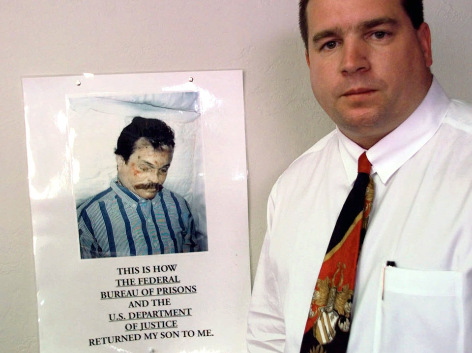 Photo - CORRECTS TO A 1997 FILE PHOTO FROM 1987 - FILE - In this 1997 file photo, Kenneth Trentadue, shown in the poster hanging in the office of Oklahoma City lawyer Scott Adams, is pictured in Oklahoma City. Prison officials maintain that Trentadue committed suicide by hanging himself. Trentadue's family and Adams claim that the bruises covering his body are inconsistent with that type of death. Starting Monday, July 28, 2014, in a federal court trial in Salt Lake City, the FBI will have to persuade a judge they've really done everything possible to find video tapes of Timothy McVeigh minutes before he parked a truck outside the Oklahoma City federal building in 1995 and detonated a bomb that killed 168 people. The trial is the culmination of a nearly two-decade long quest by Salt Lake City attorney Jesse Trentadue to explain his brother's mysterious jail cell death 19 years ago in Oklahoma. (AP Photo/J. Pat Carter, File)
