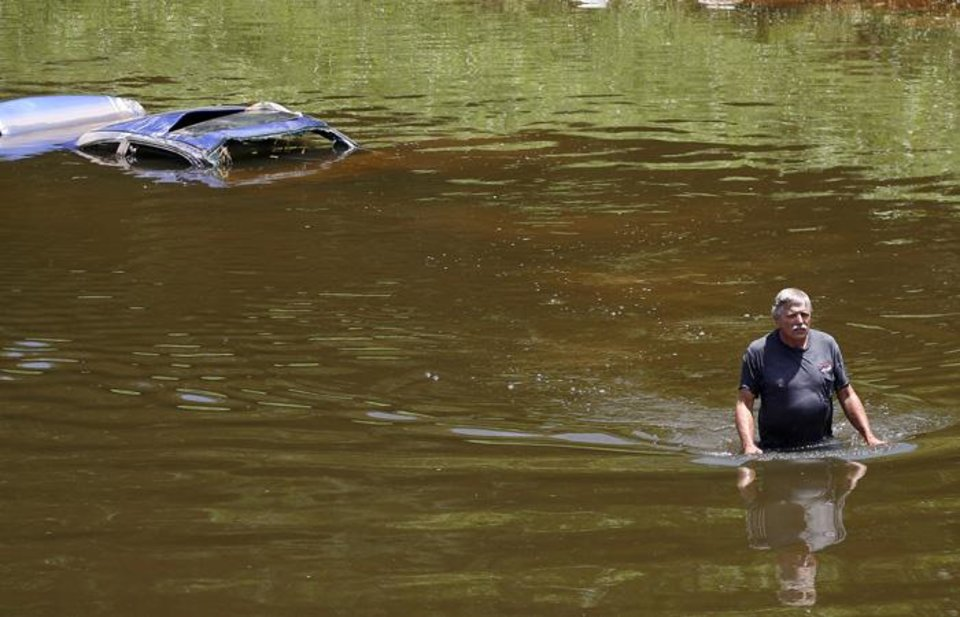 Photo -  CAR RECOVERY / RECOVER / FLASH FLOODS / TORRENTIAL RAIN / FLOOD / FLOODING / AFTERMATH: Robert Channler of Car Cab Wrecker Service wades through the river after checking the vehicals VIN number. Cars were found in the Oklahoma River on Thursday June 17th, 2010. Photo by Mitchell Alcala.  ORG XMIT: KOD