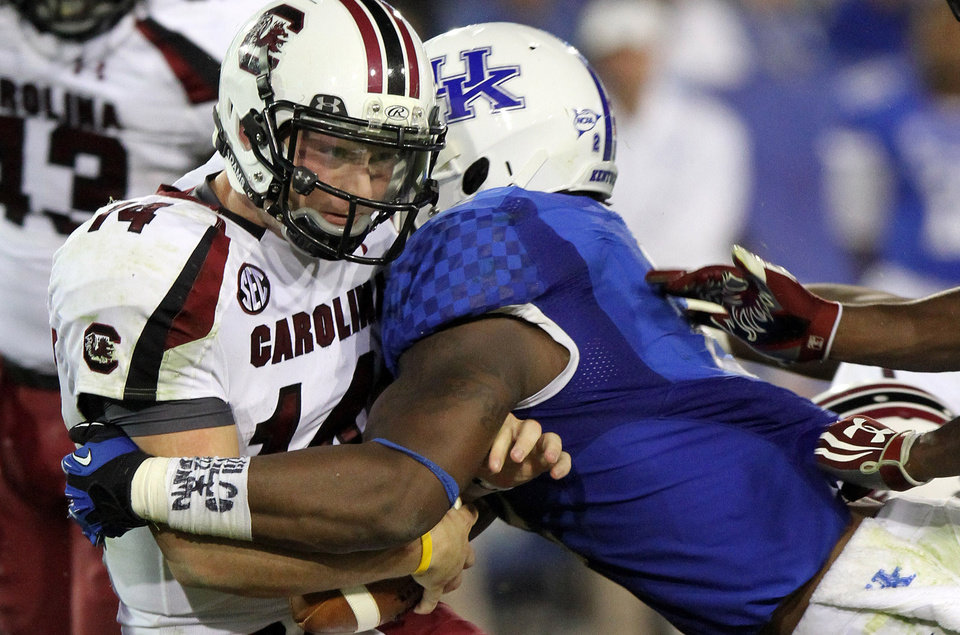Photo - FILE - In this Sept. 29, 2012, file photo, South Carolina's Connor Shaw, left, is sacked by Kentucky's Alvin Dupree during the fourth quarter of an NCAA college football game in Lexington, Ky. Dupree and Za'Darius Smith are back for their senior seasons, good news for Kentucky in many ways. (AP Photo/James Crisp, File)
