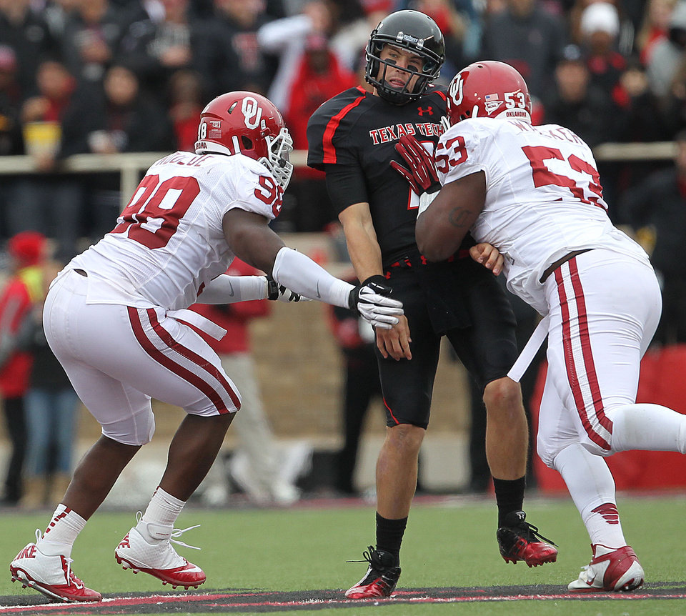 Photo -   Texas Tech's Seth Doege is hit by Oklahoma's Casey Walker (53) as Chuka Ndulue (98) nears Doege during an NCAA college football game in Lubbock, Texas, Saturday, Oct. 6, 2012. (AP Photo/Lubbock Avalanche-Journal, Stephen Spillman) LOCAL TV OUT