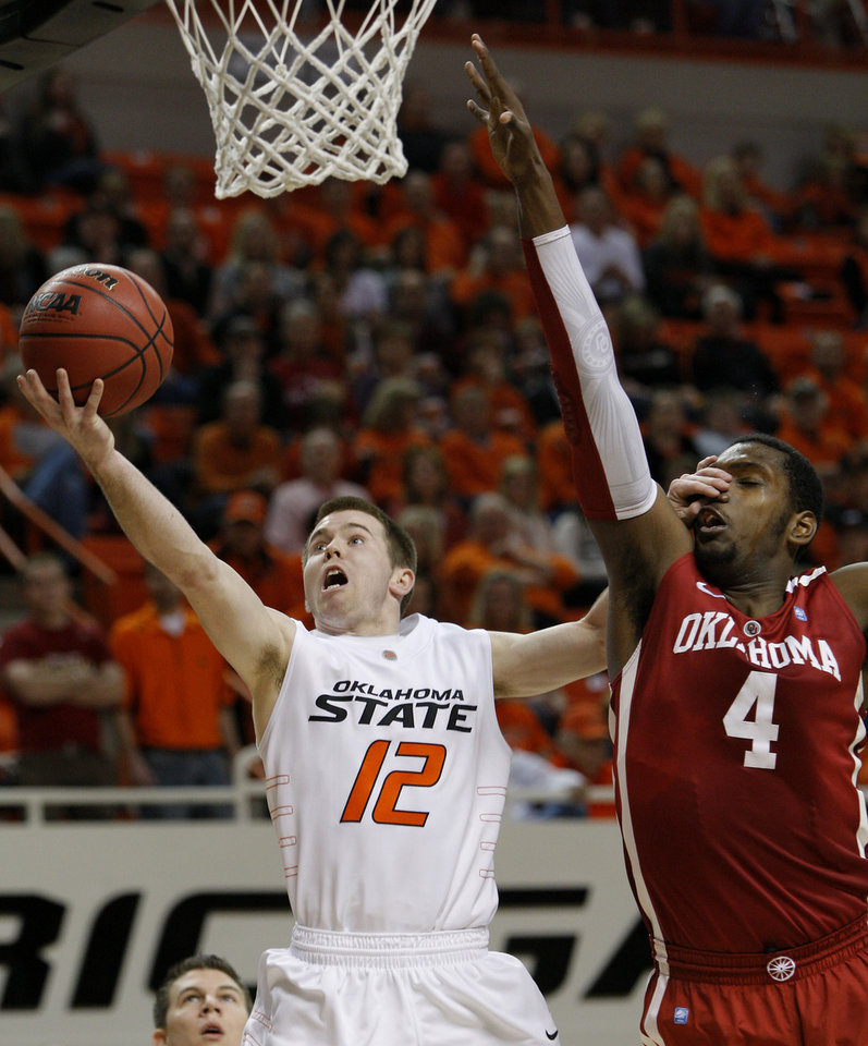 Photo - Oklahoma State's Keiton Page (12)Êgoes past Oklahoma's Andrew Fitzgerald (4)during the Bedlam men's college basketball game between the University of Oklahoma Sooners and Oklahoma State University Cowboys at Gallagher-Iba Arena in Stillwater, Okla., Saturday, February, 5, 2011. Photo by Bryan Terry, The Oklahoman