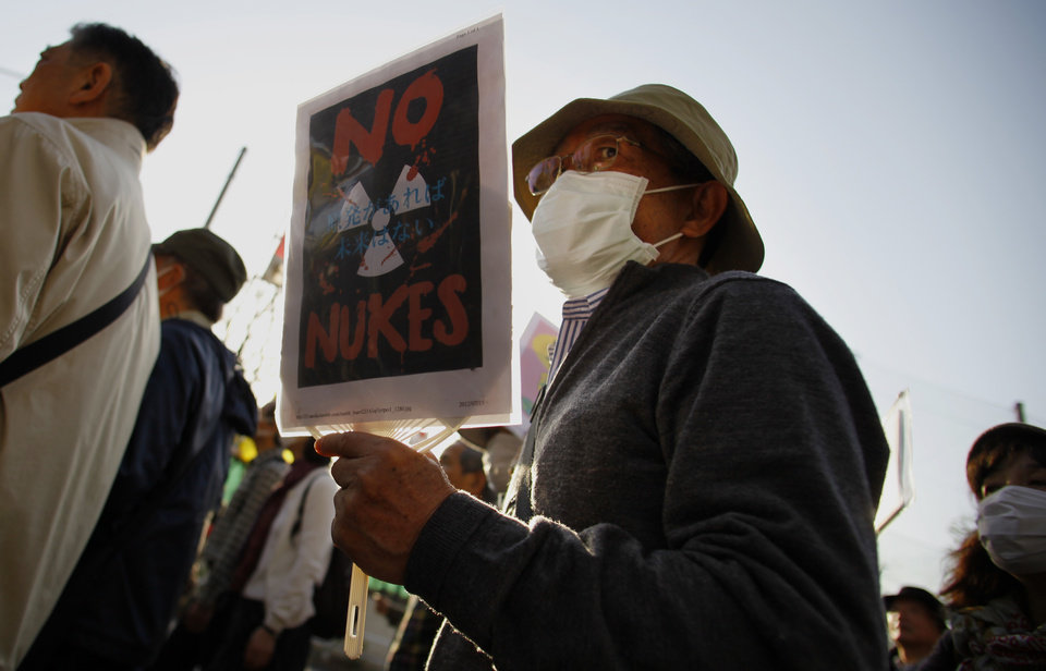 Photo - A protester holds a placard during an anti-nuclear demonstration in Tokyo, Saturday, March 9, 2013. Gathering on a weekend ahead of the second anniversary of the March 11 quake and tsunami that sent Fukushima Dai-ichi plant into multiple meltdowns, demonstrators said they would never forget the world's worst nuclear catastrophe, and expressed alarm over the government's eagerness to restart reactors. (AP Photo/Junji Kurokawa)