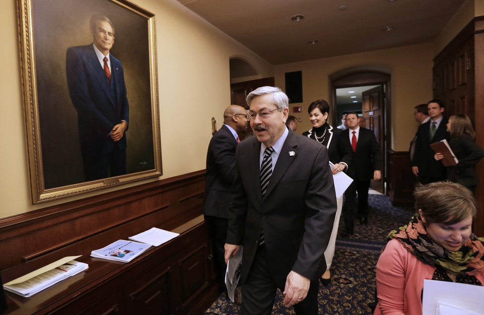 Photo - Iowa Gov. Terry Branstad walks in to a news conference during the opening day of the Iowa Legislature, Monday, Jan. 14, 2013, at the Statehouse in Des Moines, Iowa. (AP Photo/Charlie Neibergall)