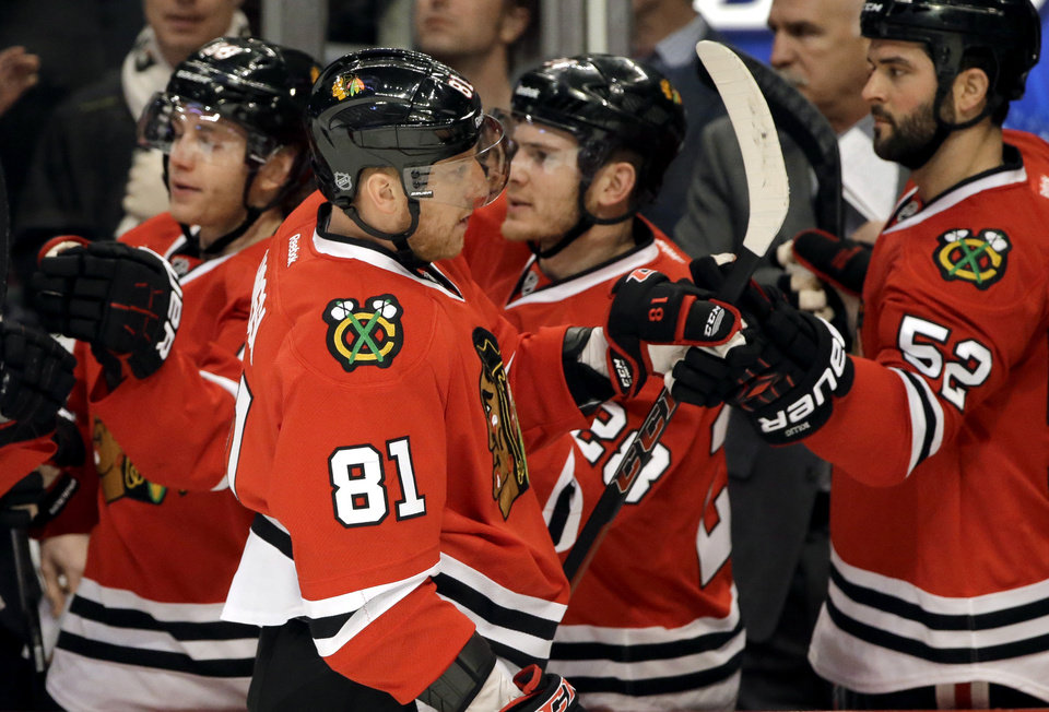 Photo - Chicago Blackhawks' Marian Hossa (81) is congratulated by teammates after his goal during the first period of an NHL hockey game against the Anaheim Ducks in Chicago, Friday, Jan. 17, 2014. (AP Photo/Nam Y. Huh)