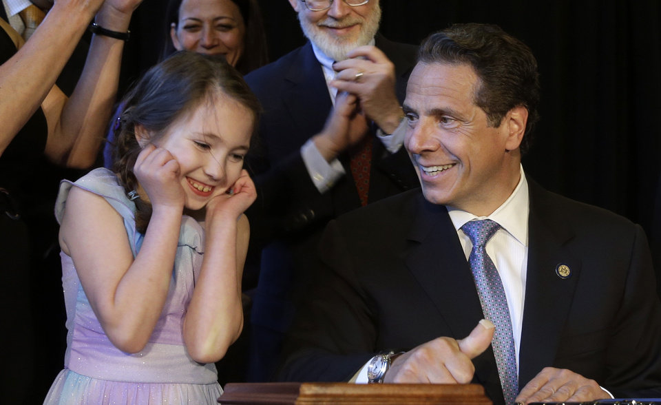 Photo - New York Governor Andrew Cuomo, right, gets some help from Amanda Houser, 10, while signing a ceremonial bill to establish a medical marijuana program in New York, Monday, July 7, 2014. New York has become the 23rd state in the U.S. to authorize medical marijuana,  though the state's program is one of the nation's most restrictive.  Cuomo signed the measure into law on Saturday and held the formal signing ceremony on Monday to highlight the new law.  When the program gets up and running in about 18 months, patients with diseases including AIDS, cancer and epilepsy will be able to obtain non-smokeable versions of the drug. Instead, the drug must be ingested or administered through a vaporizer or oil base. Houser, who has Dravet syndrome, may benefit from medical marijuana.(AP Photo/Seth Wenig)