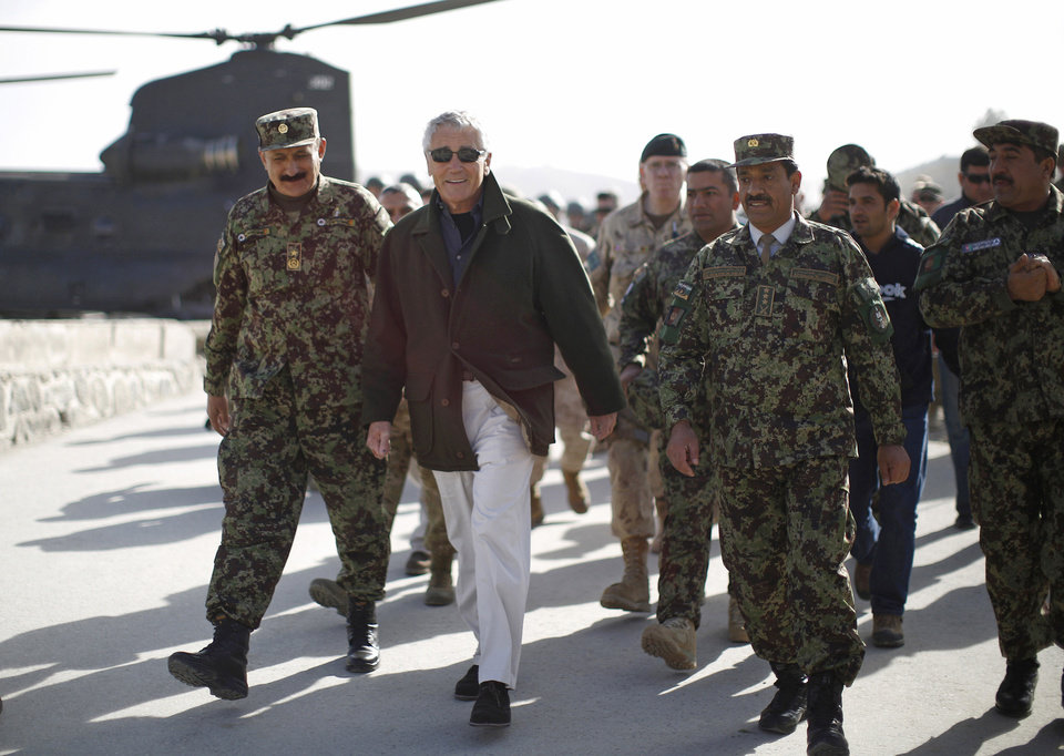 Photo - U.S. Secretary of Defense Chuck Hagel, second left, walks with Afghan Brig. Gen. Aminullah Patyani, left, commander of the Kabul Military Training Center, upon his arrival at the facility in Kabul, Afghanistan, Sunday, March 10, 2013. Hagel is on his first trip to Afghanistan as defense secretary. (AP Photo/Jason Reed, Pool)
