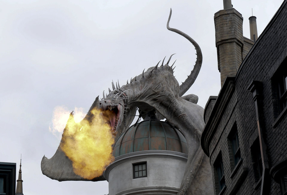 Photo - This June 19, 2014 file photo shows a dragon breathing fire from atop Gringnotts Bank during a preview of Diagon Alley at the Wizarding World of Harry Potter at Universal Orlando, in Orlando, Fla. For a second day in a row, visitors waited up to five hours to get on the ride, Harry Potter and the Escape from Gringotts, located in the new Diagon Alley section of Universal Studios. On Tuesday, July 8, on the first day Diagon Alley was open to the public, visitors waited for as long as seven hours. (AP Photo/John Raoux, File)