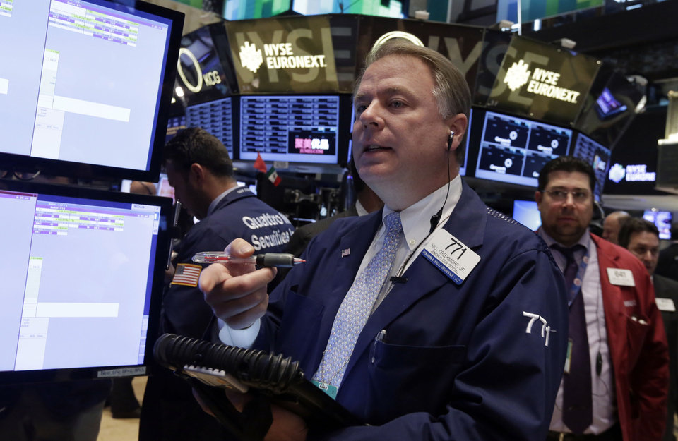 Photo - Trader F. Hill Creekmore, center, works on the floor of the New York Stock Exchange Monday, May 19, 2014. U.S. stocks drifted between small gains and losses in early trading Monday in the wake of news on a possible merger between AT&T and DirecTV. (AP Photo/Richard Drew)