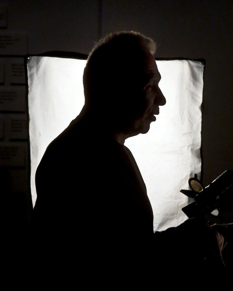 Photo - Fashion designer Jean Paul Gaultier is silhouetted in a television light after an interview about the installation of his Brooklyn Museum's