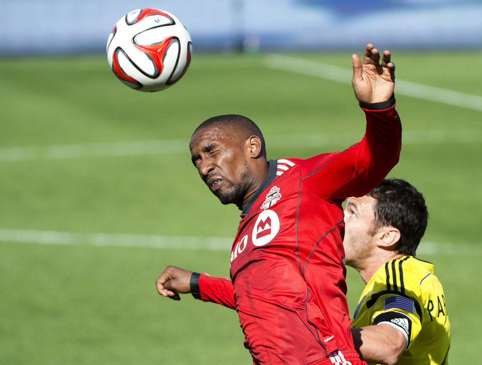 Photo - Toronto FC forward Jermain Defoe, left, heads the ball past Columbus Crew defender Michael Parkhurst during the first half of an MLS soccer game in Toronto on Saturday, May 31, 2014. (AP Photo/The Canadian Press, Nathan Denette)
