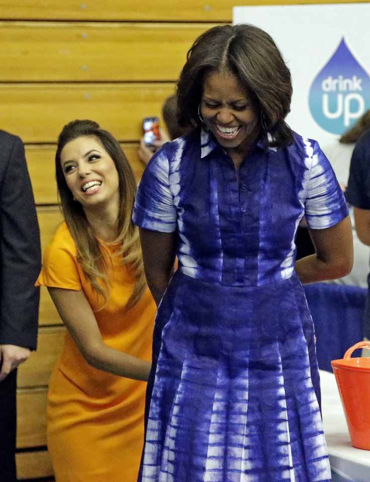 Photo - First Lady Michelle Obama and actress Eva Longoria participate in an event at Watertown High School to encourage people to drink more water, Thursday, Sept. 12, 2013, in Watertown, Wis. (AP Photo/Morry Gash)