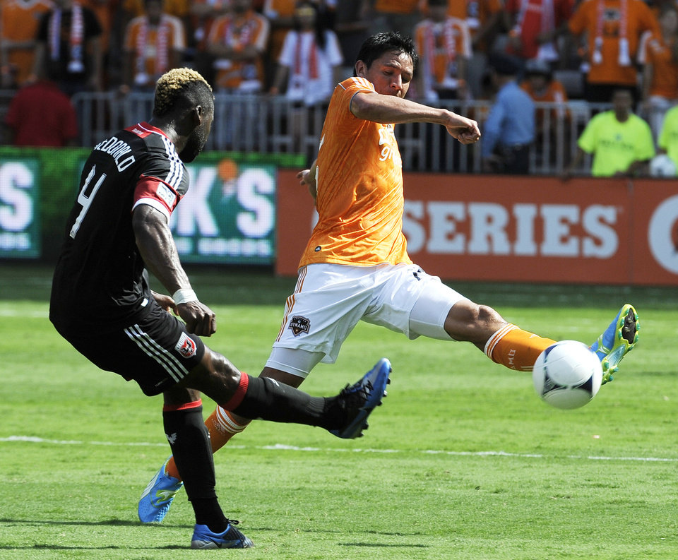 Houston Dynamo\'s Brian Ching, right, tries to get the ball past D.C. United\'s Brandon McDonald (4) in the first half of an MLS soccer match, Saturday, May 12, 2012, in Houston. (AP Photo/Pat Sullivan)