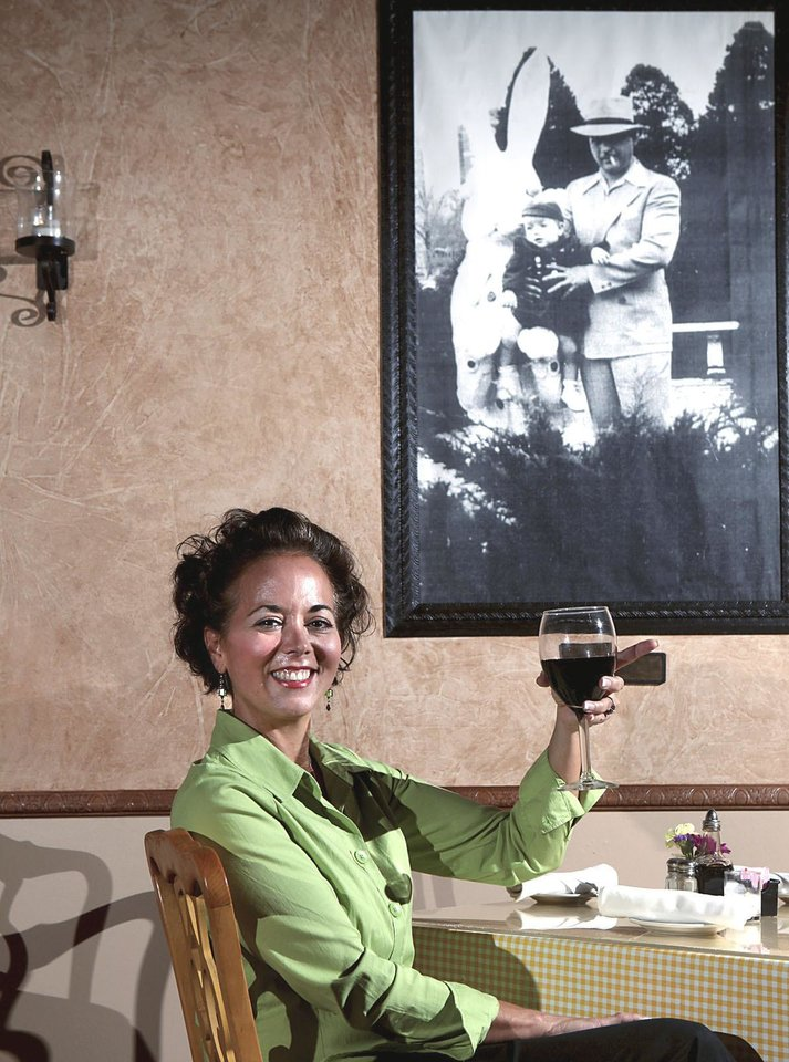 Photo - Sitting at a table under a picture of her Uncle Vito at her restaurant, Vito's Ristorante, owner Cathy Cummings lifts a glass of wine.  Photo By John Clanton, The Oklahoman