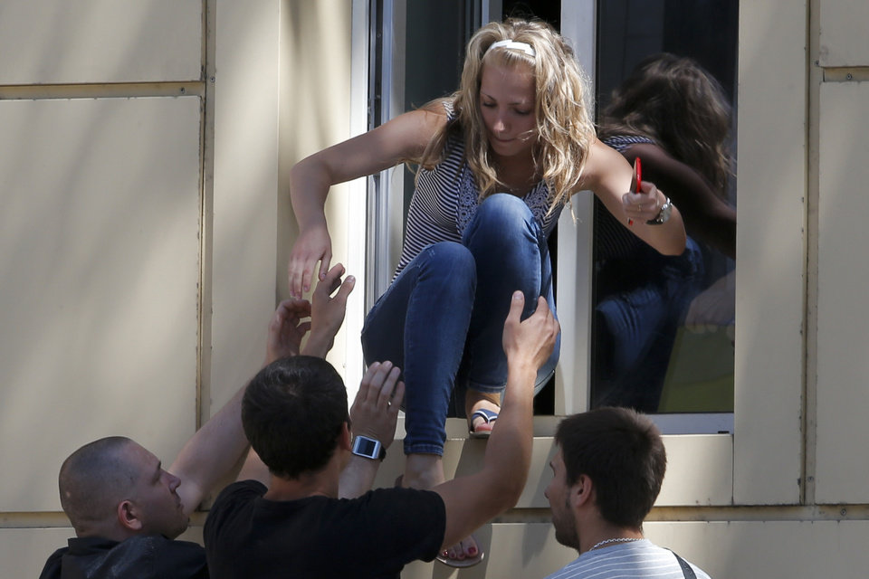 Photo - People are evacuated from a hospital during fighting near a regional police department in downtown Donetsk, eastern Ukraine, Tuesday, July 1, 2014. Ukraine renewed its attacks against armed pro-Russia separatists Tuesday after the president called off a unilateral cease-fire, carrying out air and artillery strikes against rebel positions in eastern Ukraine. (AP Photo/Dmitry Lovetsky)