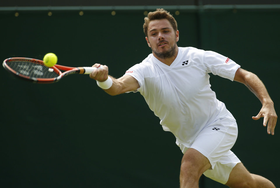 Photo - Stan Wawrinka of Switzerland plays a return to Joao Sousa of Portugal during their first round match at the All England Lawn Tennis Championships in Wimbledon, London, Tuesday, June 24, 2014. (AP Photo/Alastair Grant)
