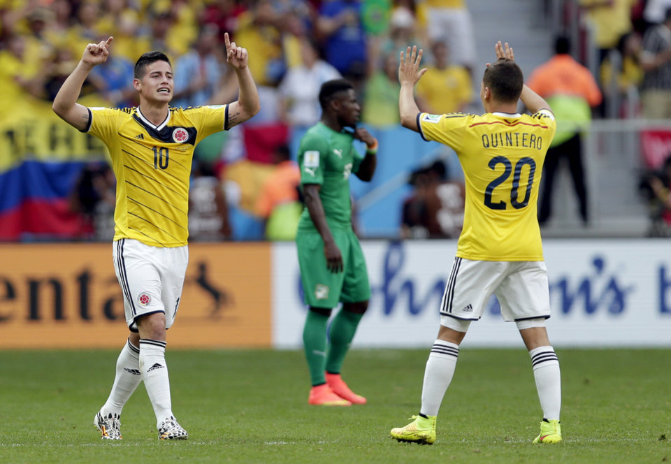 Photo - Colombia's James Rodriguez (10) celebrates with Juan Quintero (20) after scoring his side's opening goal during the group C World Cup soccer match between Colombia and Ivory Coast at the Estadio Nacional in Brasilia, Brazil, Thursday, June 19, 2014.  (AP Photo/Marcio Jose Sanchez)