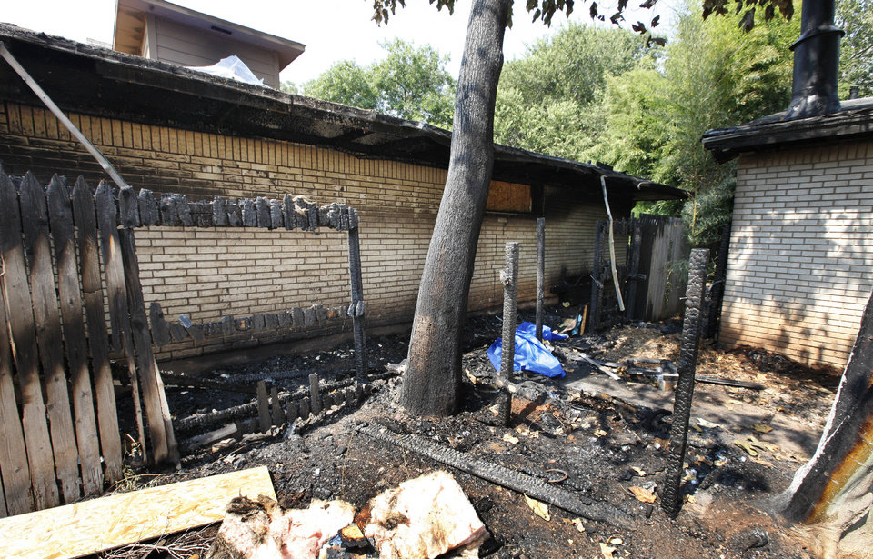 Photo - Roof damage and a charred fence that separated the homes at 1819 and 1825 NW 42 in Oklahoma City. About midnight Sunday, a fire broke out in trash bins between the two homes. Photo by Paul B. Southerland, The Oklahoman  PAUL B. SOUTHERLAND - PAUL B. SOUTHERLAND