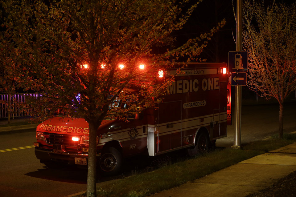 Photo - A King Co. EMS vehicle is shown staged several blocks from the scene of an overnight shooting that police said left five people dead, Monday, April 22, 2013, at an apartment complex in Federal Way, Wash. (AP Photo/Ted S. Warren)