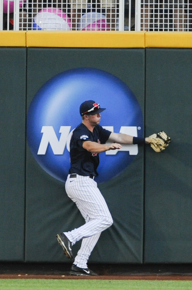 Photo - Mississippi right fielder J.B. Woodman bumps into the wall after catching a fly ball hit by TCU's Derek Odell in the fourth inning of an NCAA baseball College World Series elimination game in Omaha, Neb., Thursday, June 19, 2014. (AP Photo/Eric Francis)