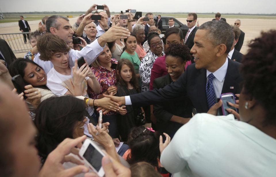 Photo - President Barack Obama greets guests on the tarmac upon his arrival on Air Force One at Austin-Bergstrom International Airport, Thursday, May 9, 2013 in Austin, Texas. (AP Photo/Pablo Martinez Monsivais)