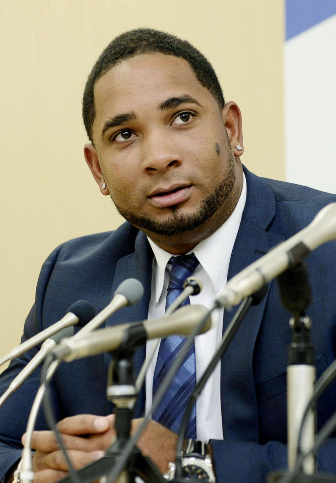 Photo - Yakult Swallows slugger Wladimir Balentien speaks during a press conference in Tokyo Wednesday, Jan. 29, 2014. Balentien has apologized to his fans, several days after pleading not guilty to domestic violence charges in Florida. As is the custom in Japan, Balentien bowed deeply and then apologized Wednesday to his fans and teammates for the actions that led to his arrest on Jan. 13. (AP Photo/Kyodo News) JAPAN OUT, MANDATORY CREDIT