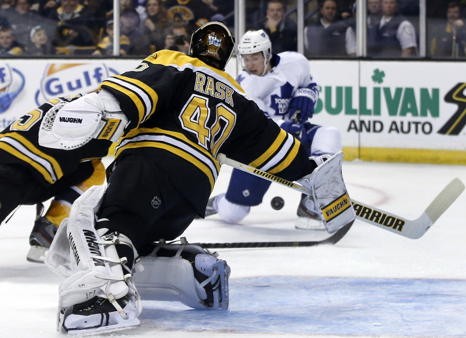 Photo - Boston Bruins goalie Tuukka Rask (40) reaches right but is unable to block a goal shot by Toronto Maple Leafs center Tyler Bozak (42) in the first period of an NHL hockey game in Boston, Tuesday, Jan. 14, 2014. (AP Photo/Elise Amendola)