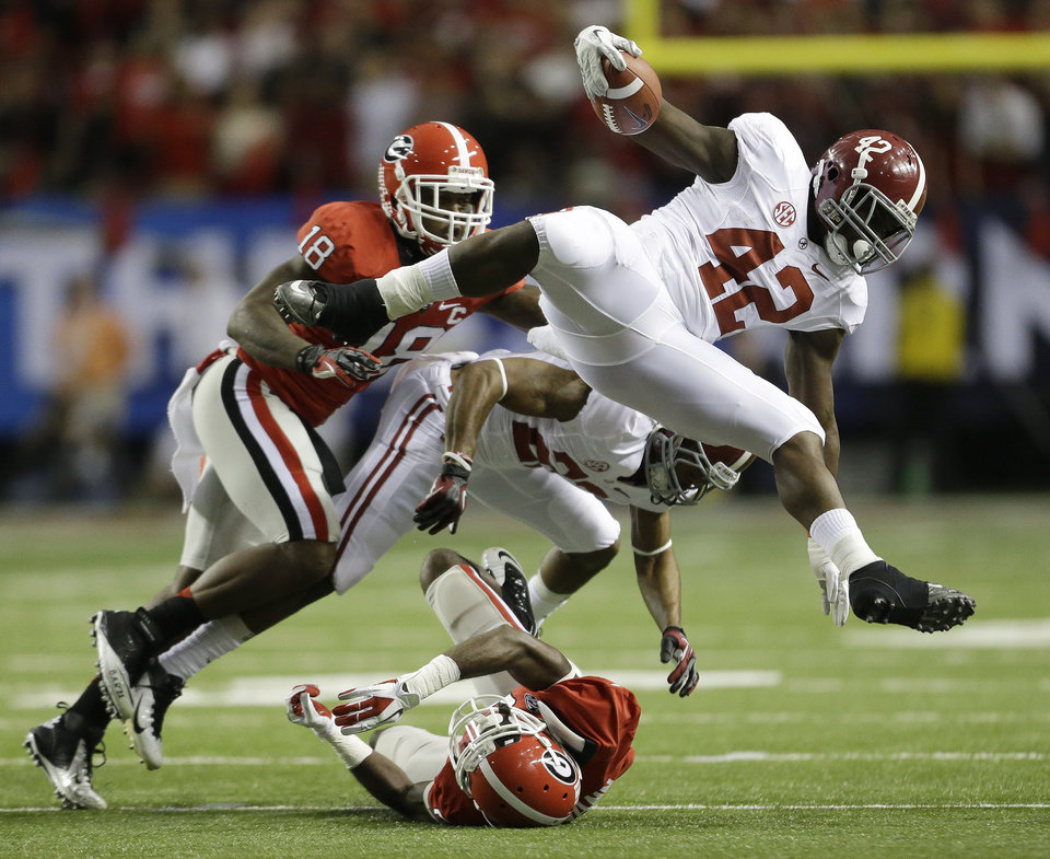Photo - Alabama running back Eddie Lacy (42) leaps over a Georgia defender during the first half of the Southeastern Conference championship NCAA college footballgame, Saturday, Dec. 1, 2012, in Atlanta. (AP Photo/David Goldman)