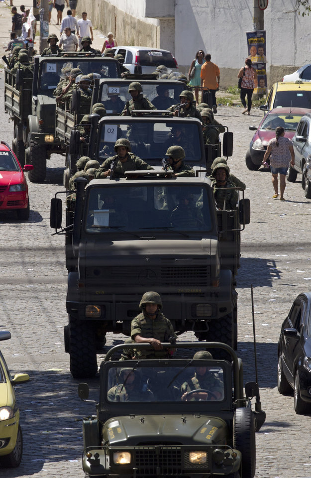 Soldiers patrol during municipal elections in the Complexo da Mare slum in Rio de Janeiro, Brazil, Sunday, Oct. 7, 2012. Voters across Latin America's biggest country are electing mayors and municipal council members. (AP Photo/Silvia Izquierdo)