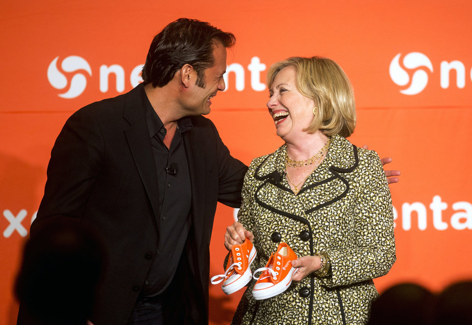 Nexenta CEO Tarkan Maner, left, presents former Secretary of State Hillary Rodham Clinton with a pair of his company\'s trademark orange sneakers during the Nexenta OpenSDx Summit Thursday, Aug. 28, 2014, in San Francisco. (AP Photo/Noah Berger)
