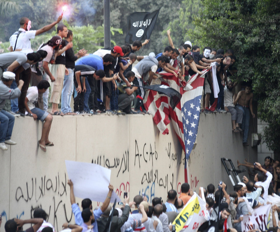 Photo - FILE - In this Sept. 11, 2012 file photo, protesters destroy an American flag pulled down from the U.S. embassy in Cairo, Egypt, during a protest of a film deemed offensive of Islam. 2012 was a year of storms, of raging winds and rising waters, but also broader turbulence that strained our moorings. And old enmities and grievances resurfaced in the Middle East, clouding the legacy of the 2011 Arab spring. (AP Photo/Mohammed Abu Zaid, File)