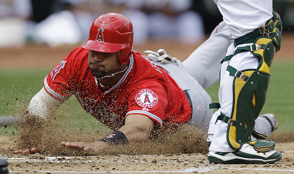 Photo -   Los Angeles Angels' Albert Pujols slides to score against the Oakland Athletics' in the third inning of a baseball game, Wednesday, Sept. 5, 2012, in Oakland, Calif. Pujols scored on a single by Howie Kendrick. (AP Photo/Ben Margot)