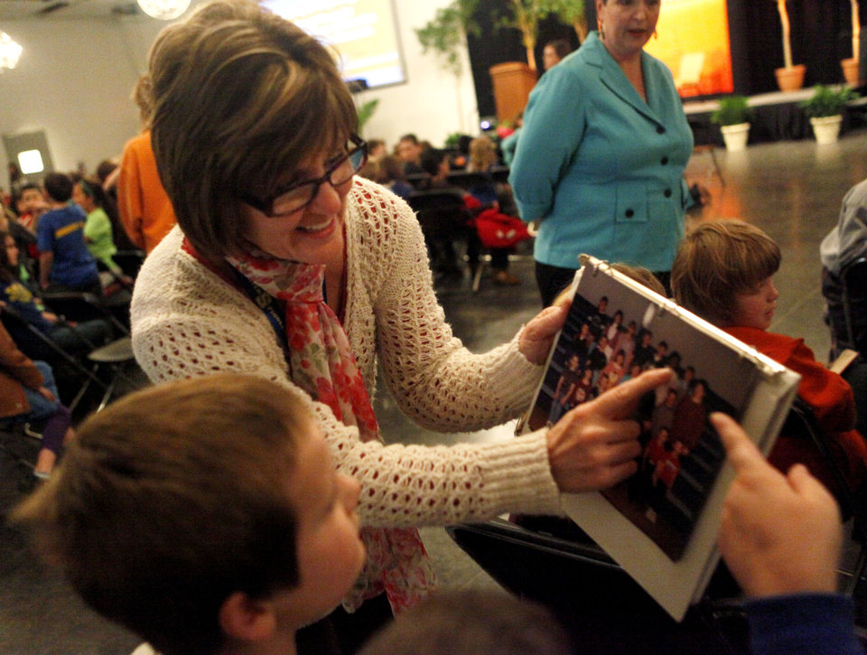Photo -  Kelly Johnson, third-grade teacher at Highland Park elementary in Stillwater, shows a student a picture Nina Davuluri's third-grade class after Davuluri gave a speech to Stillwater third grade students Thursday at the Wes Watkins Center. Davuluri lived part of her childhood in Ada before eventually moving to New York. Photo by KT King, for The Oklahoman   KT King -  KT King, The Oklahoman