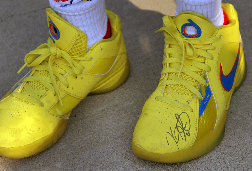 Photo - A Thunder fan wears Kevin Durant autographed shoes during the first round NBA playoff game between the Oklahoma City Thunder and the Denver Nuggets on Sunday, April 17, 2011, in Oklahoma City, Okla. Photo by Chris Landsberger, The Oklahoman