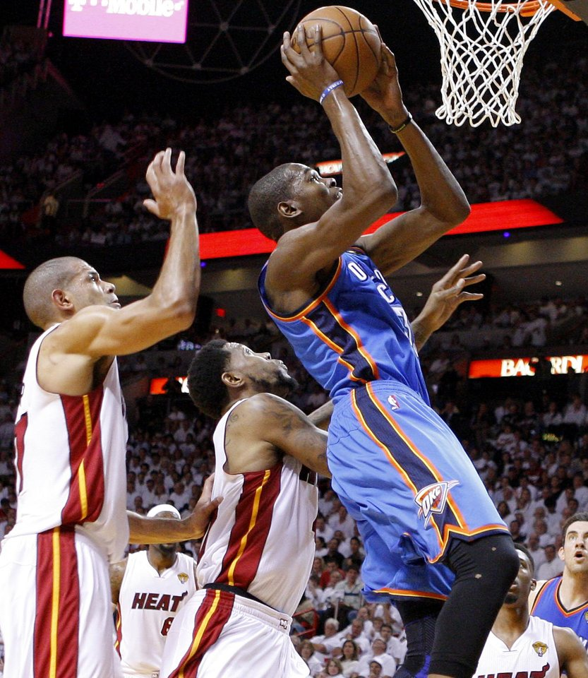 Photo - Oklahoma City's Kevin Durant (35) goes past Miami's Udonis Haslem, center, and Shane Battier during Game 4 of the NBA Finals between the Oklahoma City Thunder and the Miami Heat at American Airlines Arena, Tuesday, June 19, 2012. Photo by Bryan Terry, The Oklahoman